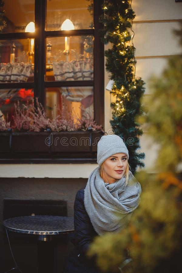 Woman in black coat and gray scarf in night city light royalty free stock photography