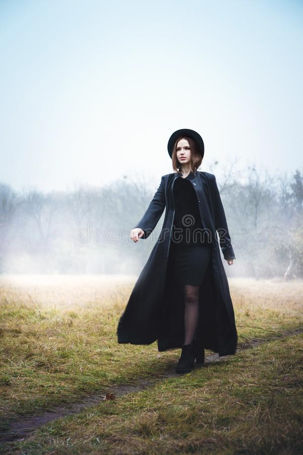 Confident woman in a black coat walking down the road stock images