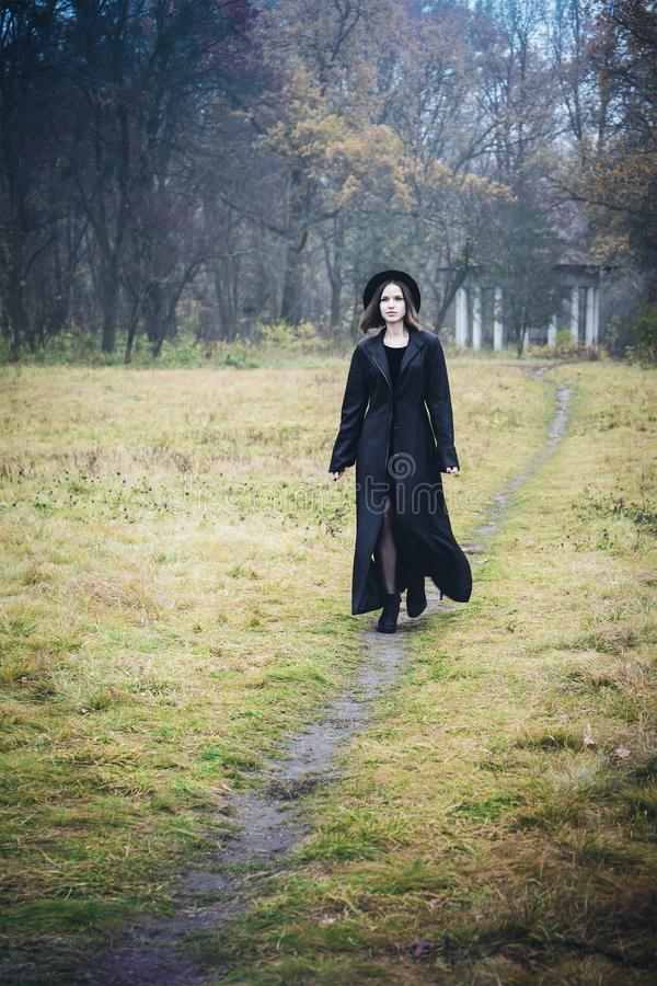 Woman in a black coat on the road stock photos