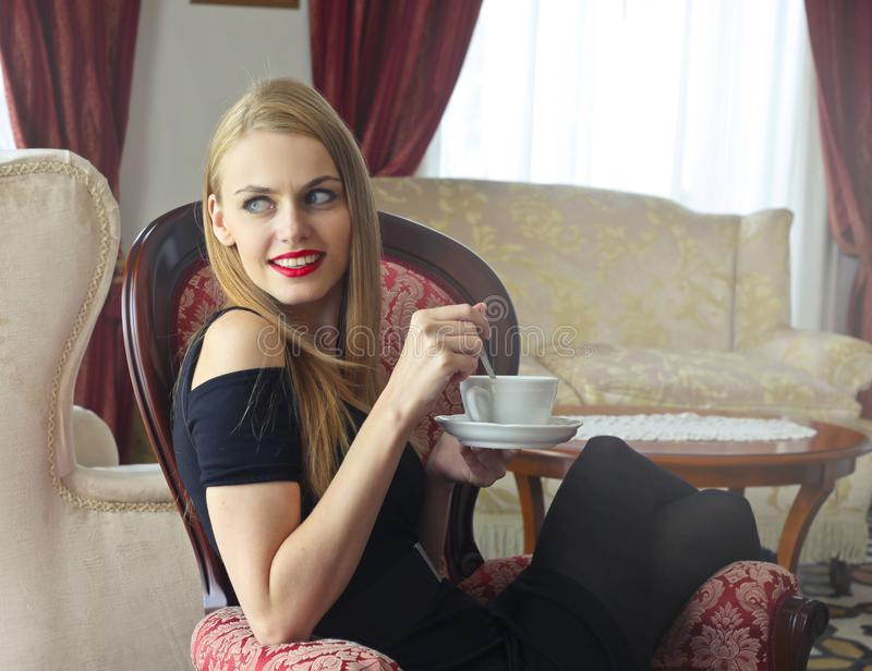 Woman in Black Cold-shoulder Dress Holding Tea Cup With Saucer stock photography