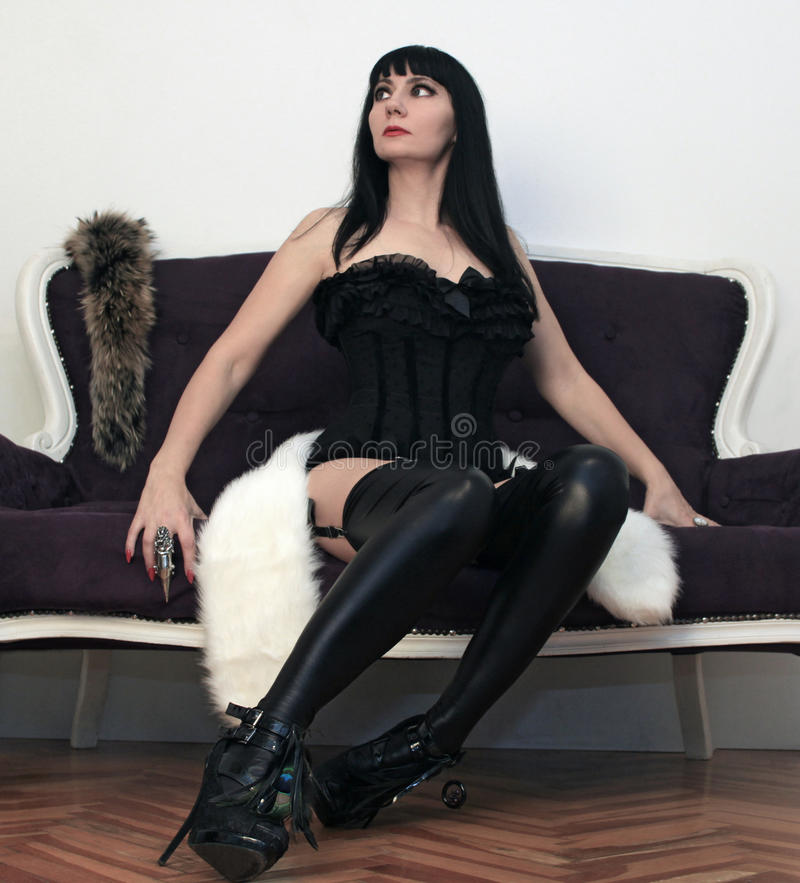 Woman in black corset sitting on sofa