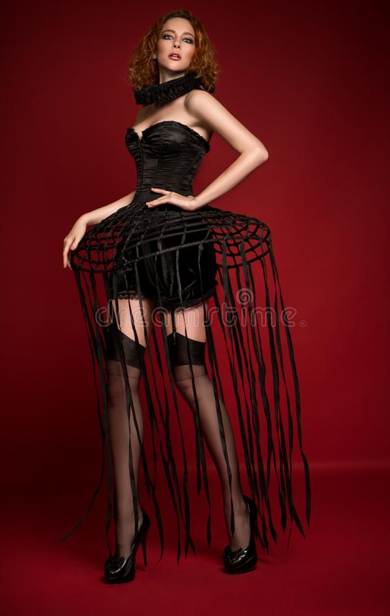 Woman in black corset, skirt with stripes stock photo