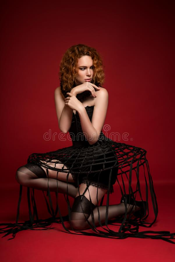 Woman in black corset, skirt with stripes, frill and stockings stock photography