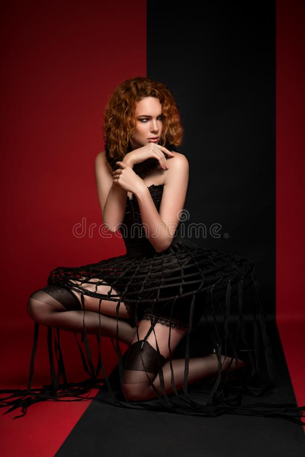 Woman in black corset, skirt with stripes, frill and stockings royalty free stock photography