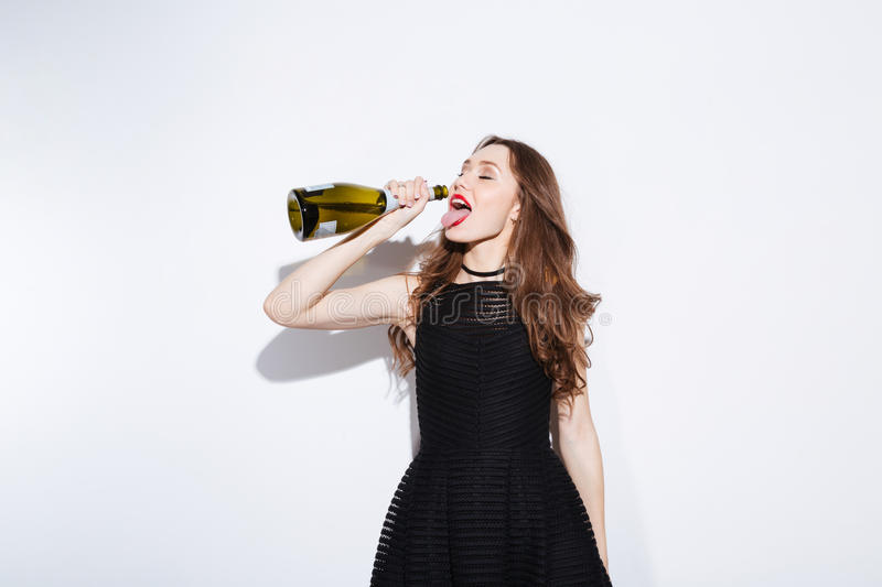 Woman in black dress drinking champagne from bottle stock image