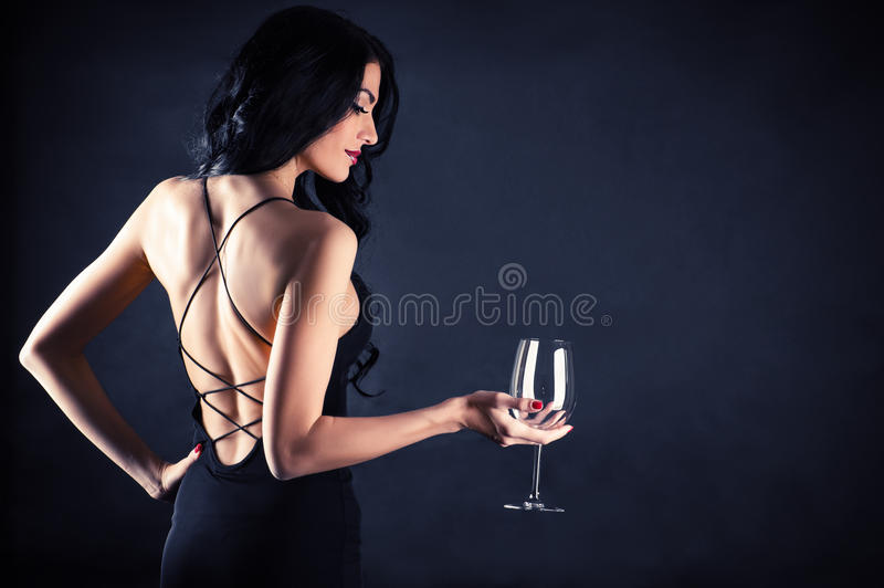 Woman in a black dress with a glass in hand. Beautiful woman in a black dress with a glass in hand stock photos
