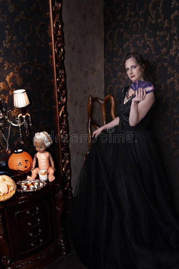 Woman in black dress for Halloween with a fan of cards in hand. Halloween, a girl in a black dress in a Gothic environment in a dark room, causes fear. woman in royalty free stock photo
