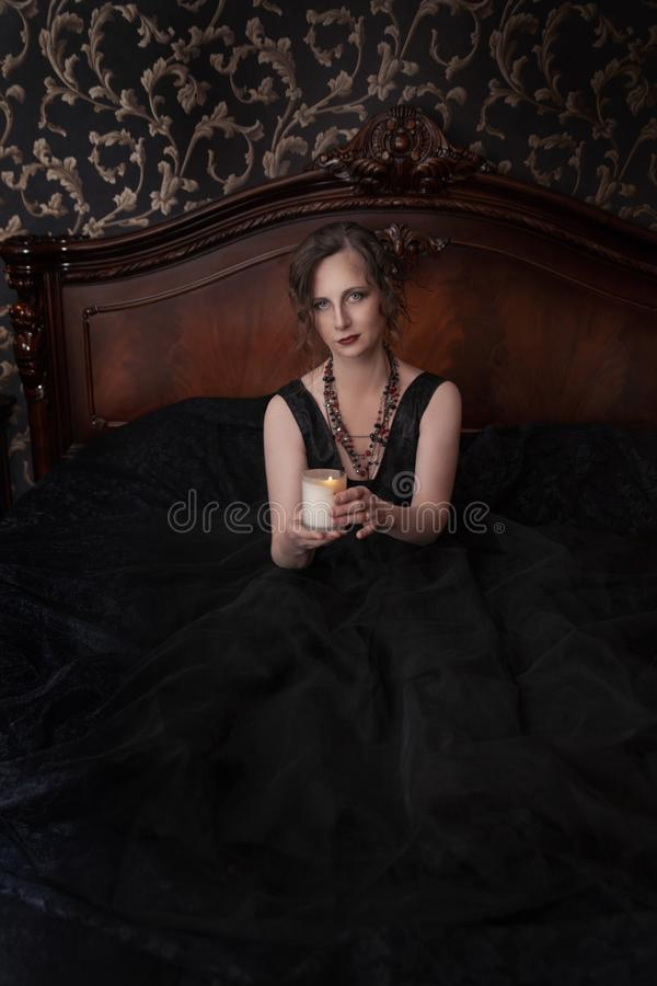 Woman in black dress for Halloween holding candles in her hands. Halloween, a girl in a black dress in a Gothic environment in a dark room, causes fear. woman in royalty free stock photos