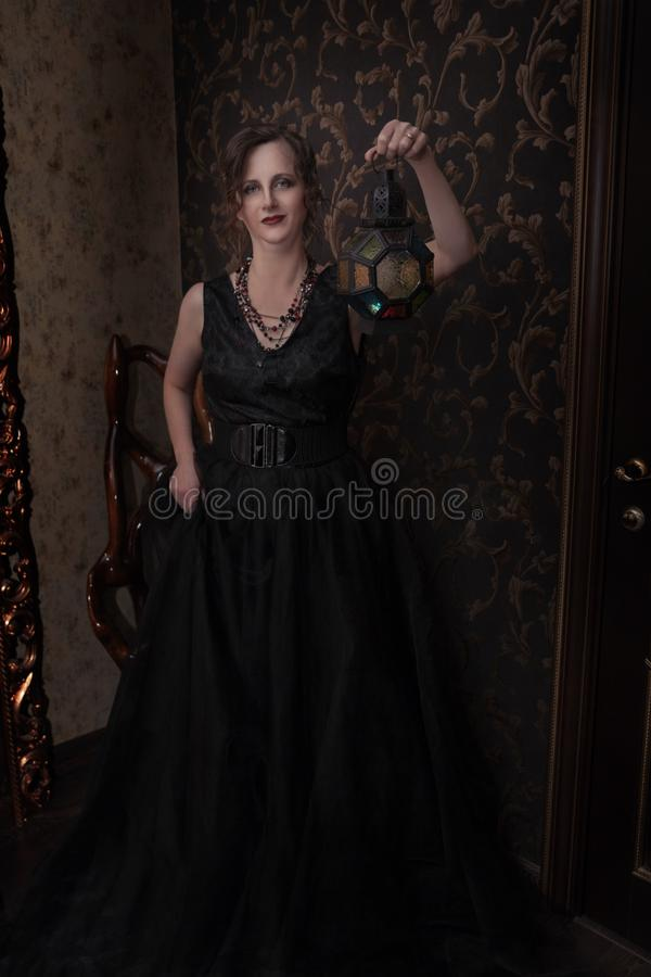 A woman in a black dress for Halloween holding a lantern in her hands. Halloween, a girl in a black dress in a Gothic environment in a dark room, causes fear. a royalty free stock image