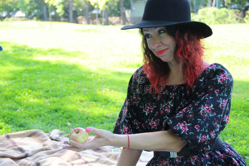 woman in a black dress and hat, with red curly hair, holds out her hand and offers an Apple stock photo
