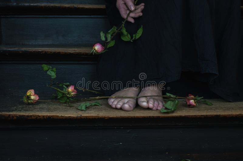 A woman in a black dress holding a bouquet of dead roses royalty free stock photo