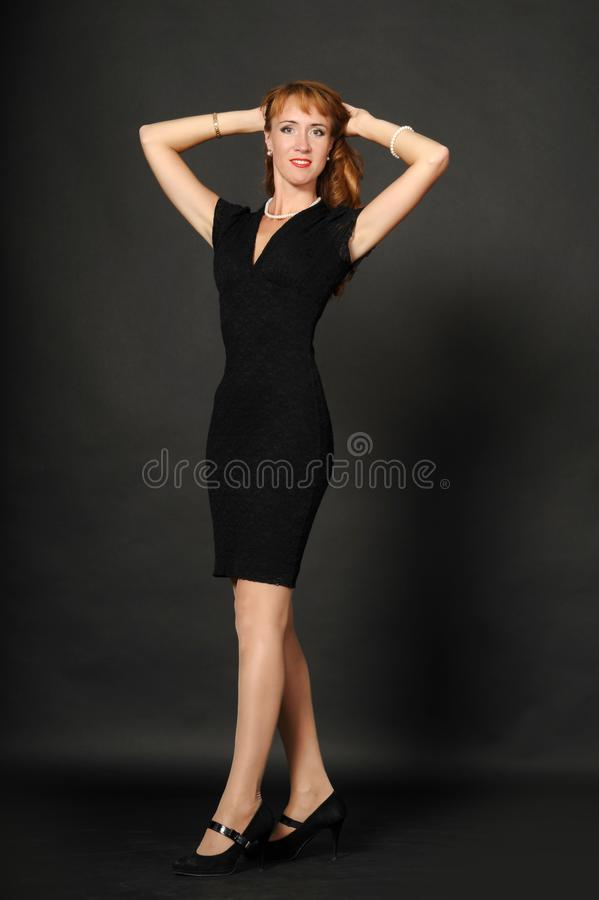 A woman in a black dress holding her hair royalty free stock photo