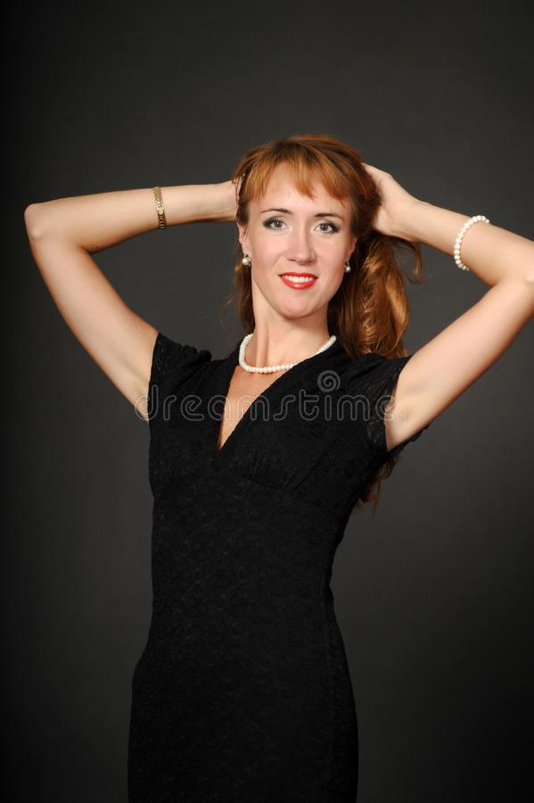 A woman in a black dress holding her hair royalty free stock photography
