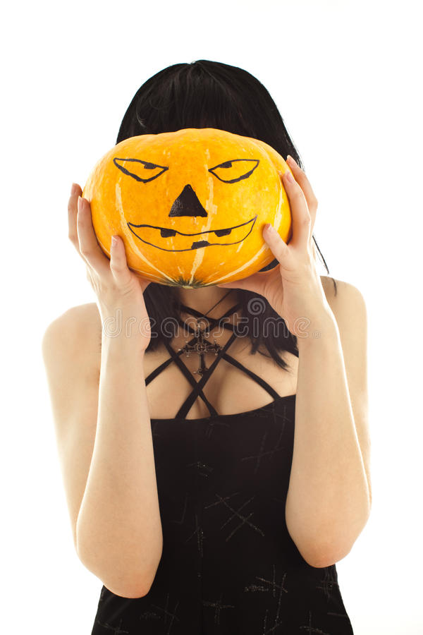 Woman in black dress holding a Jack-o'-lantern. Isolated on white stock images