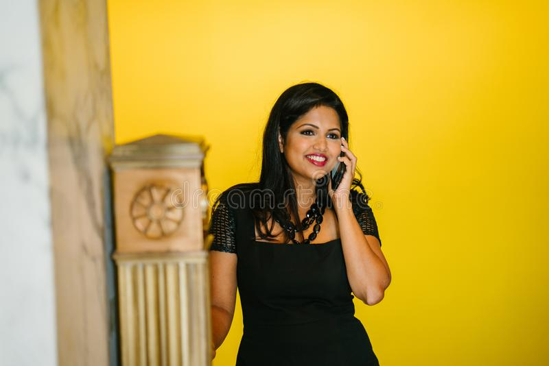 Woman in Black Dress Holding Black Phone royalty free stock image