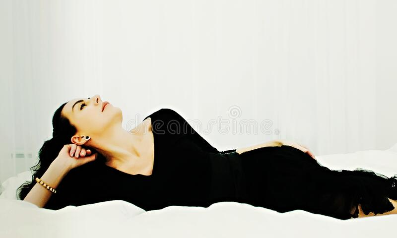 Woman in black dress lying stock images