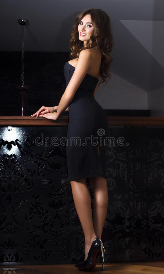Woman in black dress posing on chic interior royalty free stock photo