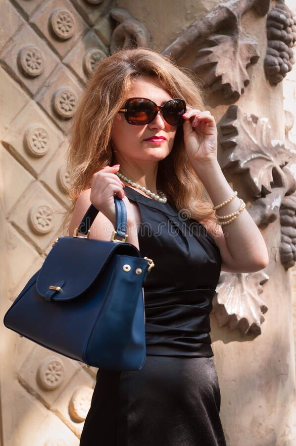Woman in black dress putting on sunglasses and holding blue bag on sidewalk near vintage building. Beautiful confident woman in black dress putting on sunglasses stock image
