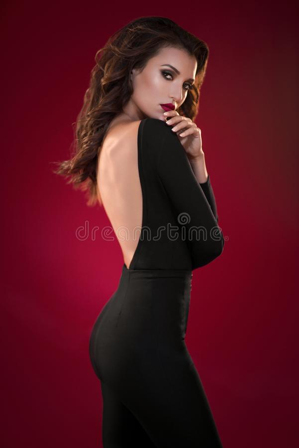 Woman in black dress on the red background stock image