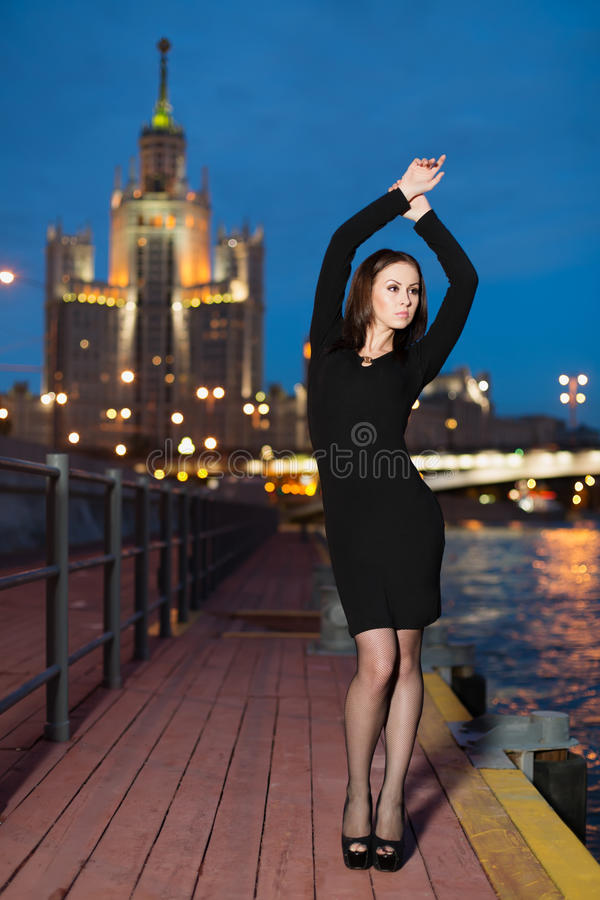Woman in black dress standing on the waterfront lifted hands stock image