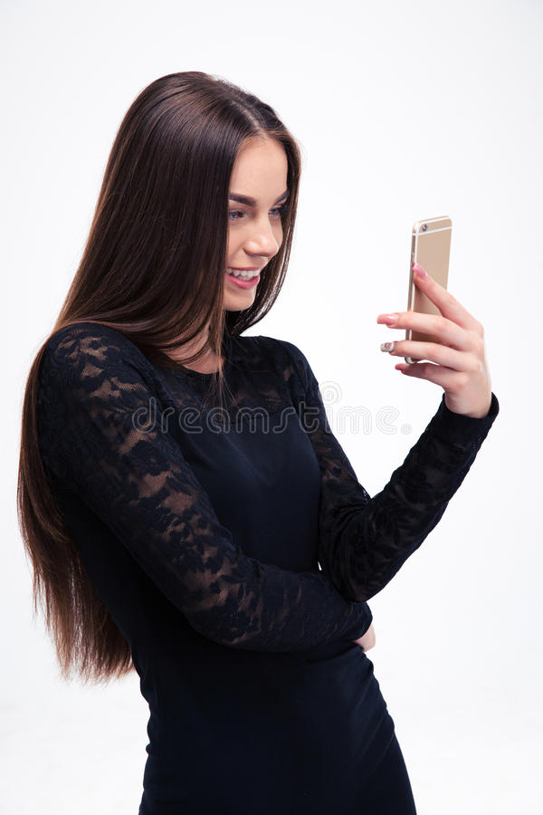 Woman in black dress using smartphone. Smiling young woman in black dress using smartphone isolated on a white background royalty free stock photos