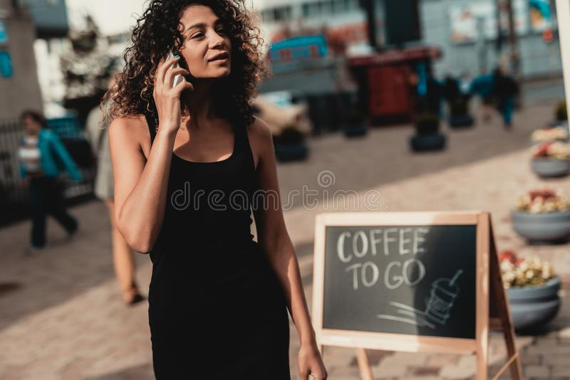 Woman in Black Dress Walking with Smartphone. Promenade in Town. Using Digital Device. Summer Day. Square in European City. Signboard on Street. Girl in Black stock images