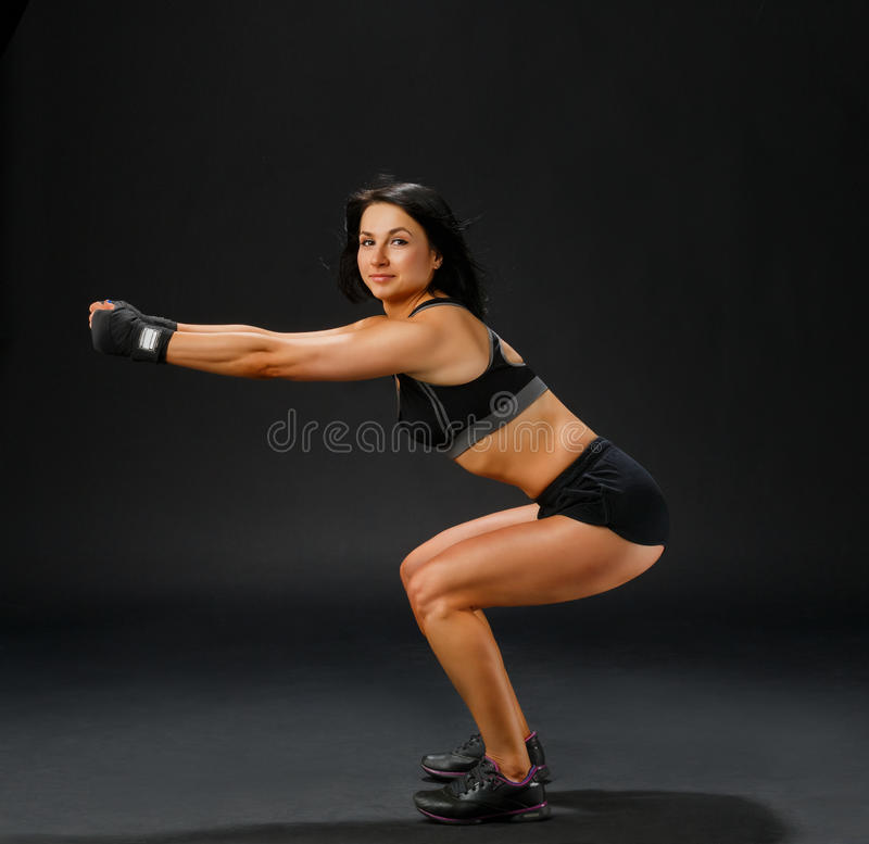Woman in black fitness suit doing squatting royalty free stock photo