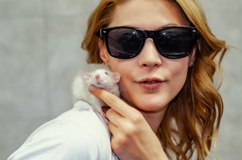 Woman in black glasses holds a white rat on her shoulder.  royalty free stock photography
