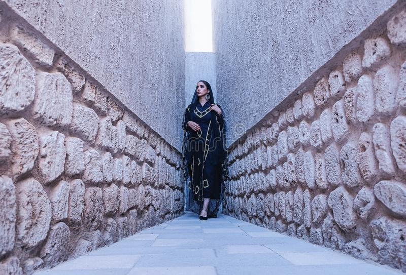 Woman in Black and Gold Traditional Dress Between Gray Concrete Walls stock photos
