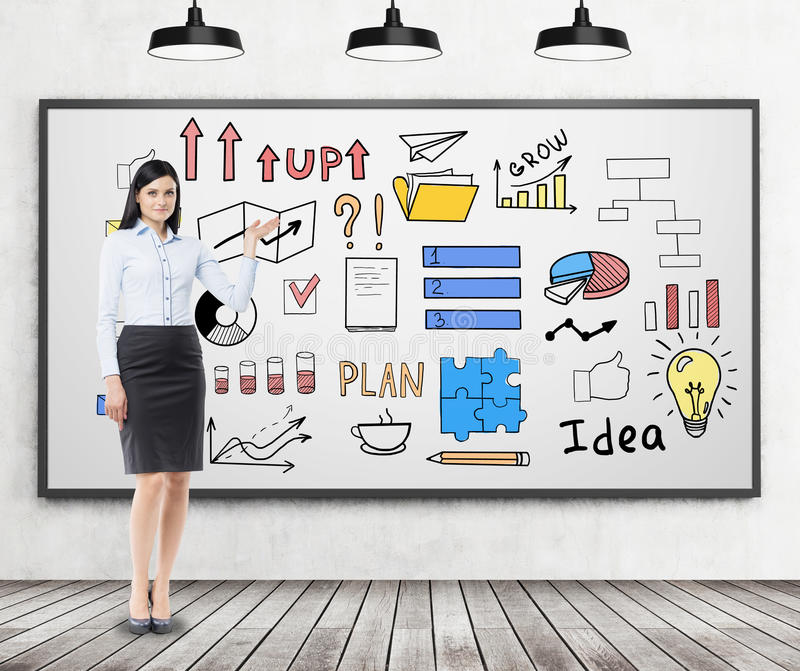 Woman with black hair and a colorful business idea sketch on a w. Woman with black hair is standing near a whiteboard with a colorful business idea sketch drawn stock photo