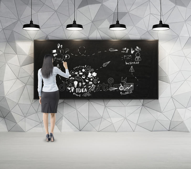 Woman with black hair is drawing sketch in dark concrete room wi royalty free stock photos