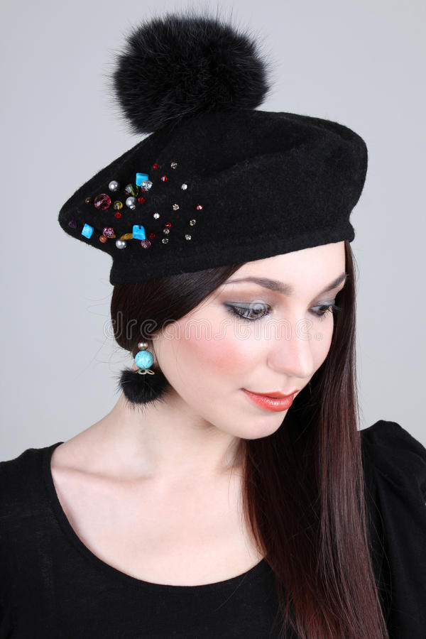 Woman in black hat and earrings