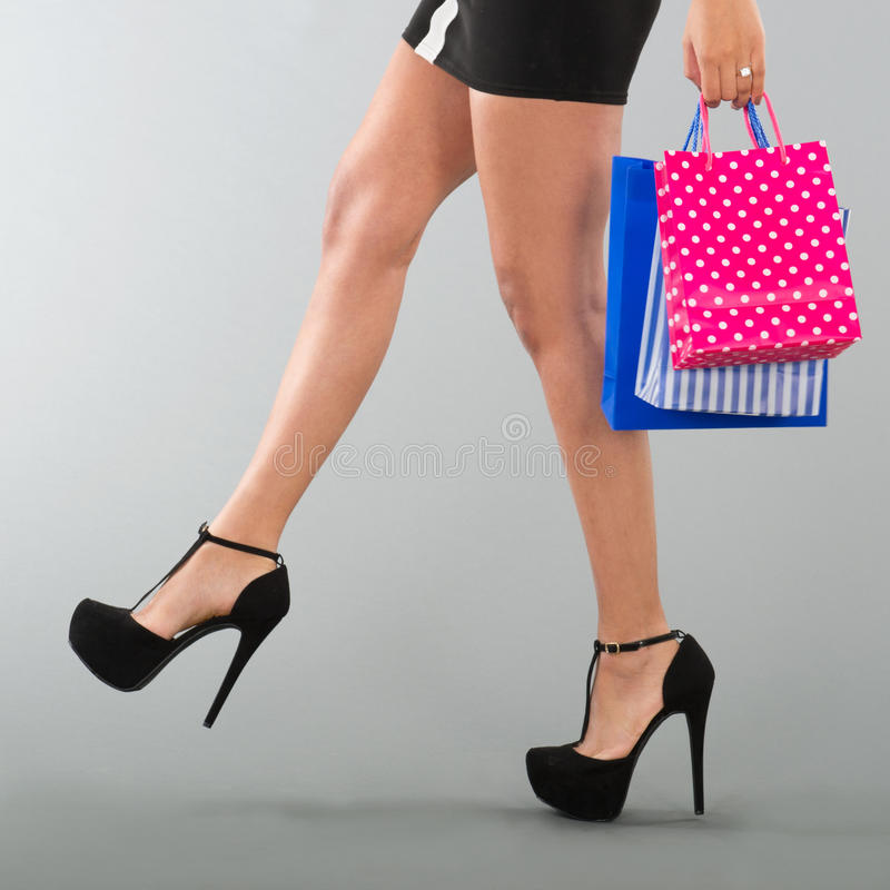 Woman with black high heels. Legs of black woman with high heels on gray background stock photography