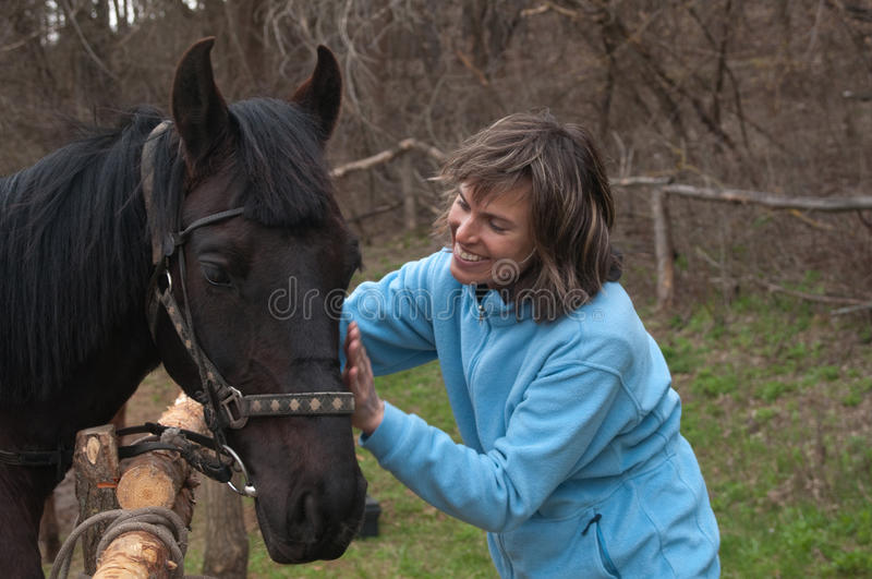 Woman And Black Horse Royalty Free Stock Image