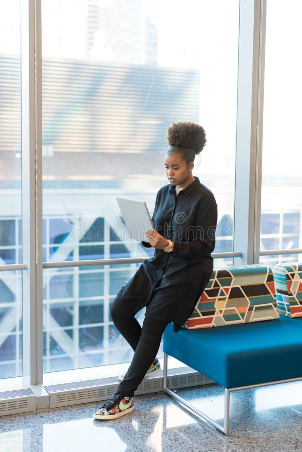 Woman in Black Jacket Standing Near Blue Sofa royalty free stock photo