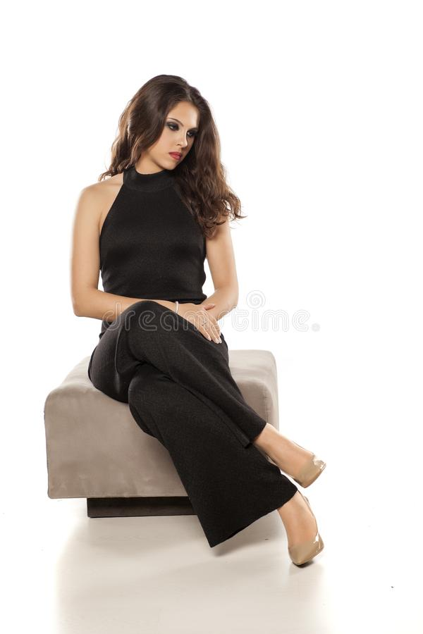 Woman in black jumpsuit sitting stock images