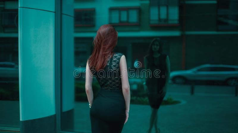 Woman in Black Lace Bodycon Dress in Front of Building Mirror royalty free stock photography