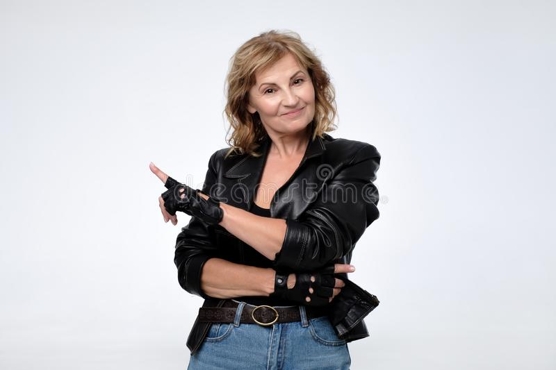 Woman in black leather jacket smiling broadly, pointing fingers away, showing something interesting stock photos