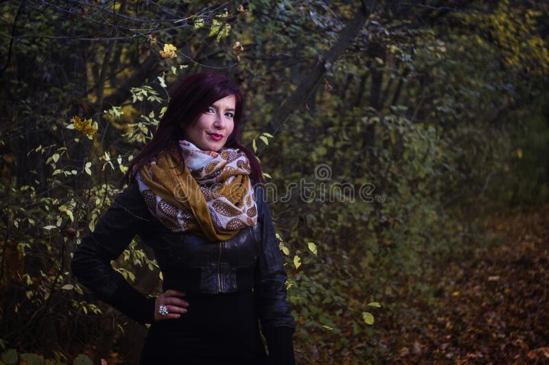 Woman in Black Leather Jacket Beside Trees royalty free stock photo