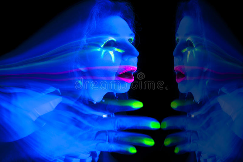 Woman black light ghost hand up. A woman lit up with ultraviolet light looks like a ghost with a reflection royalty free stock photography