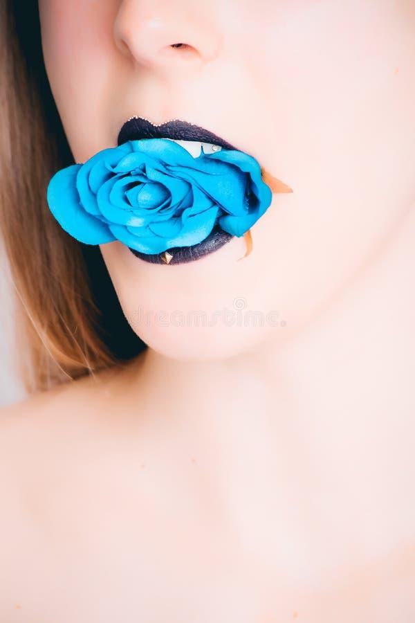 Woman With Black Lipstick Biting Blue Rose stock photo