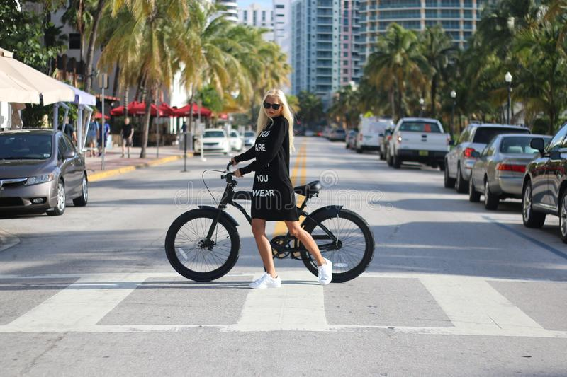 Woman In Black Long Sleeve Shirt Holding Bicycle stock photo
