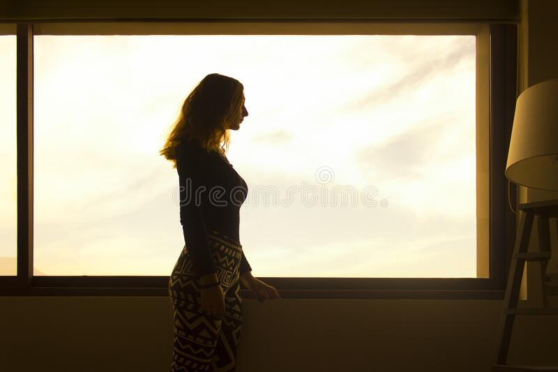 Woman in Black Long Sleeve Shirt and Tribal Leggings Standing by the Window during Daytime royalty free stock image