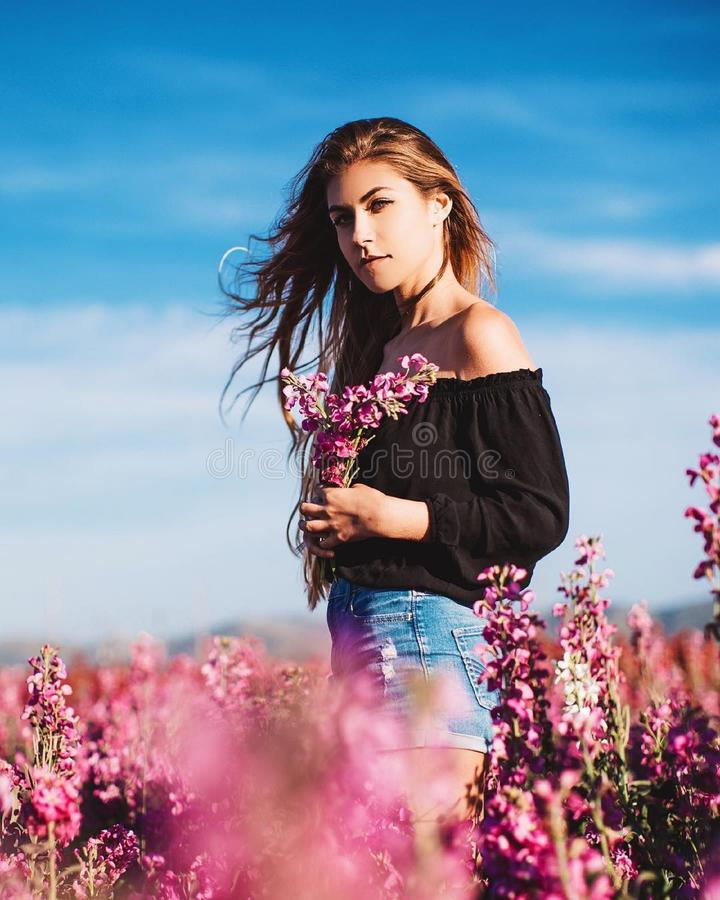 Woman in Black Long-sleeved Off-shoulder Top and Blue Denim Short Shorts Holding Flowers royalty free stock image