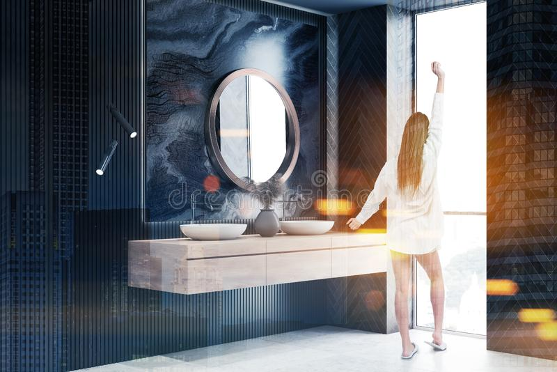 Woman in black marble bathroom, sink. Rear view of woman in nightgown standing in black marble and dark wooden bathroom with double sink and round mirror. Toned royalty free stock photography