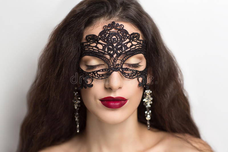 Woman with black mask. Close up portrait of Beautiful girl lady woman in a black lace mask. A mysterious stranger role play. Closed eyes professional make up red royalty free stock photography