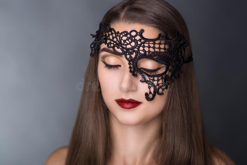 Woman in black mask. Close up portrait of Beautiful girl lady woman in a black lace mask. A mysterious stranger role play. Closed eyes professional make up red stock photos