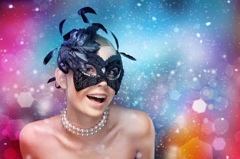 Woman with black masquerade mask with feathers. Young woman with black masquerade mask with feathers, fantasy background royalty free stock images