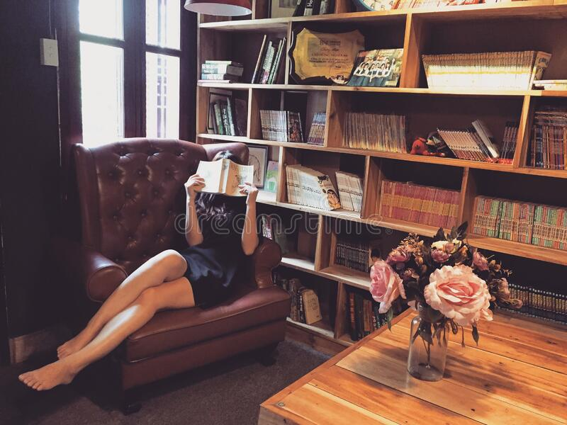 Woman in Black Mini Dress Sitting on Brown Leather Tufted Sofa Chair Beside Brown Wooden Book Shelf royalty free stock images