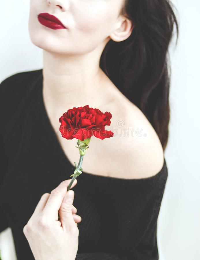 Woman in Black One-shoulder Top Holding Red Carnation royalty free stock photo